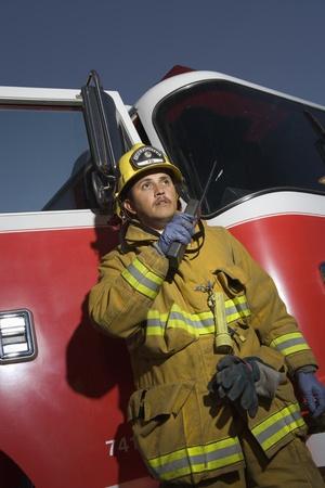 walkie talkie: Firefighter using walkie talkie by fire engine