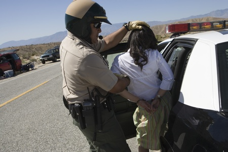 arresting: Police officer arrests female driver LANG_EVOIMAGES