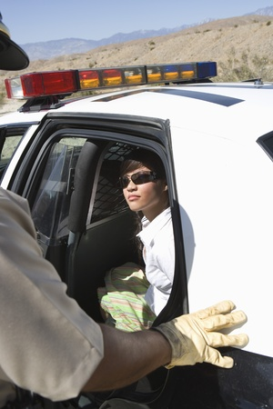 Police officer arrests female driver Stock Photo