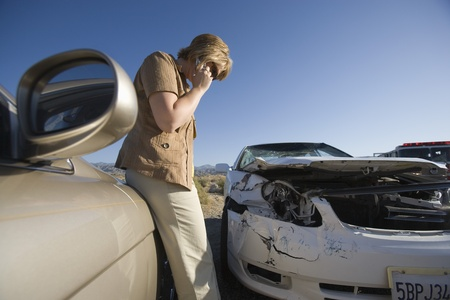 wrecked: Young woman using mobile phone by car wreckage LANG_EVOIMAGES