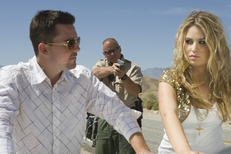 Police man aims gun at young couple Stock Photo - 12513817