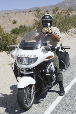 motorcycle officer: Motorcycle police officer with speed radar