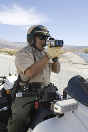 motorcycle police officer: Motorcycle police officer with speed radar