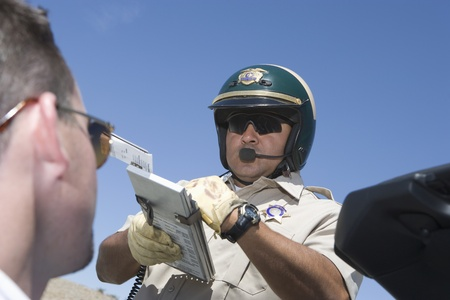 Police man writing man speeding ticket Stock Photo - 12513825