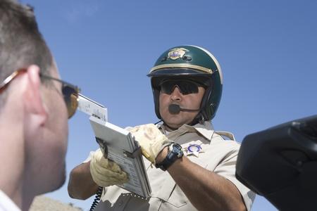 Police man writing man speeding ticket