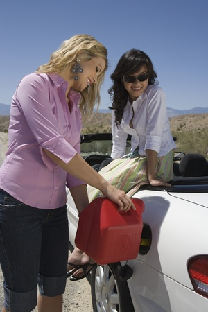 Two young women refuelling car Stock Photo - 12513829