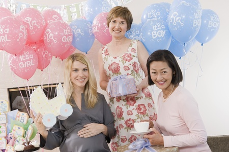 only mid adult women: Women Holding Gifts at a Baby Shower LANG_EVOIMAGES