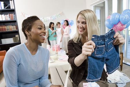 only mid adult women: Women at a Baby Shower with baby Clothes