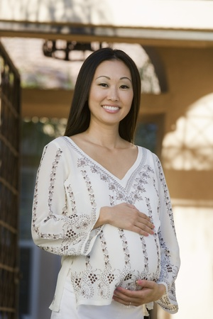 30s: Pregnant Asian WomanStanding Outside Celebrating a Baby Shower LANG_EVOIMAGES