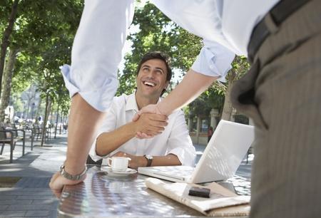 manos estrechadas: Dos hombres de negocios Reunión en Sidewalk Cafe