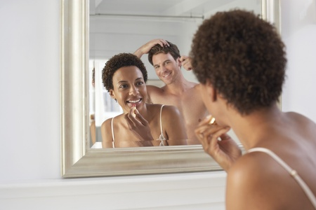 racially diverse: Couple Using Bathroom Mirror