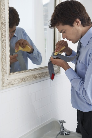 Man scrubbing stain from tie by sink Stock Photo - 12513991