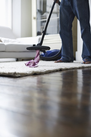 Man vacuuming tie from rug low section Stock Photo - 12513995