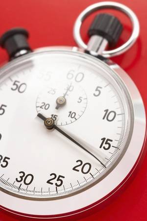 Stopwatch on red background studio shot Stock Photo - 12514055