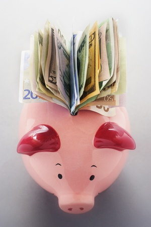Paper money coming out of piggy bank view from above Stock Photo - 12514061