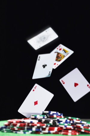 Playing cards falling on pile of gambling chips in studio Stock Photo - 12514064