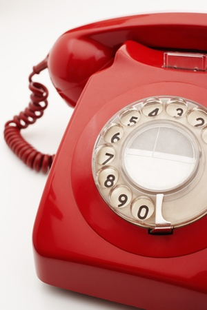 vintage style: Old fashioned red telephone in studio cropped LANG_EVOIMAGES