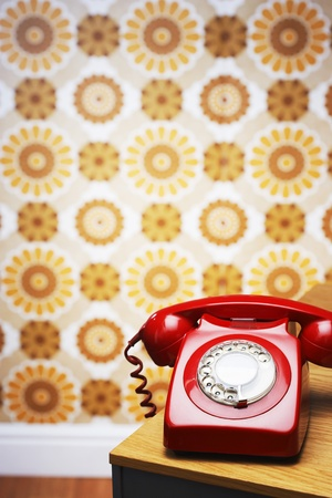 patterned wallpaper: Old fashioned red telephone on table in front of flowery wallpaper LANG_EVOIMAGES