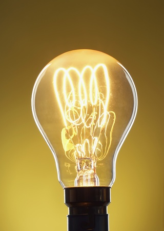 filament: Illuminated light bulb against yellow background in studio