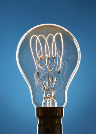 Transparent light bulb against blue background in studio Stock Photo - 12514087