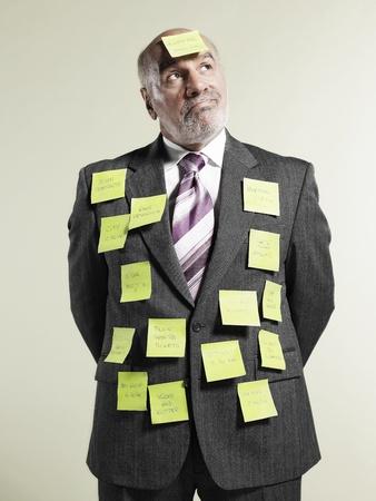 memorise: Businessman wearing sticky notes