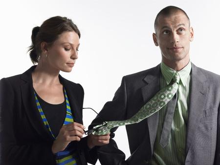 battle of the sexes: Businesswoman cleaning glasses on tie of businessman