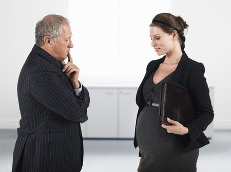 sex discrimination: Boss talking to pregnant businesswoman half length