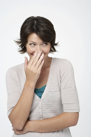 Smiling Woman standing covering face with hand Stock Photo - 12514148
