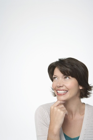 Smiling Woman looking up hand on chin Stock Photo - 12514151
