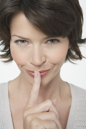 Woman with Finger on Lips grinning mischievously close-up Stock Photo