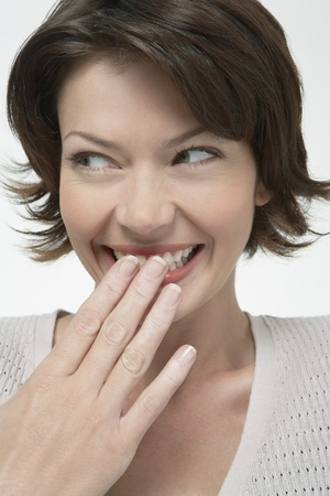 Smiling Woman covering mouth with hand looking away close-up Stock Photo - 12514155