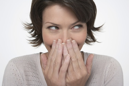 shyness: Smiling Woman covering mouth with both hands close-up