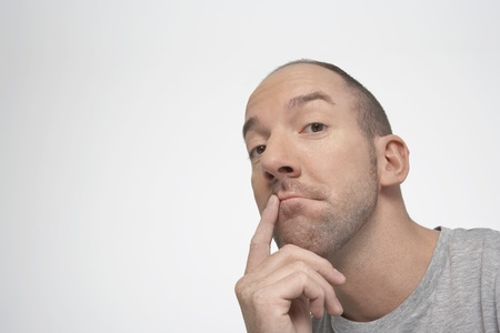 Man with finger on lips thinking Stock Photo - 12514161