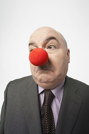 foolishness: Bald businessman Wearing Clown Nose frowning