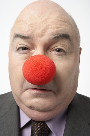 foolishness: Bald businessman Wearing Clown Nose frowning close-up