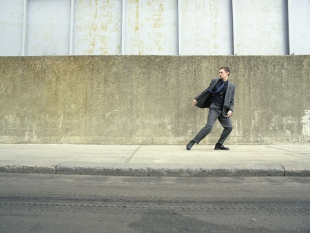 Teenager in suit running on street looking back Stock Photo - 12514196