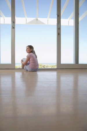 Girl sitting on floor in doorway smiling Stock Photo - 12514198