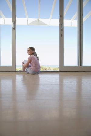 knees bent: Girl sitting on floor in doorway smiling