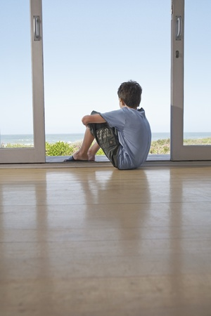 Boy sitting on floor in doorway looking at view Stock Photo - 12514197