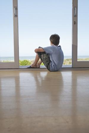 horizonte: Ni�o sentado en el suelo en la puerta mirando a la vista LANG_EVOIMAGES