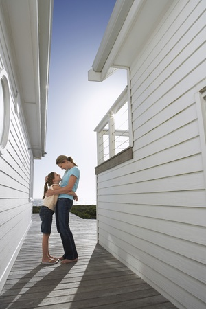 Mother embracing daughter in passageway between houses side view Stock Photo - 12514206