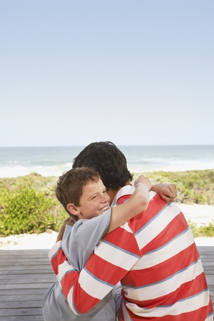Father and Son Hugging on Jetty Stock Photo - 12514207