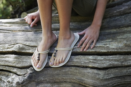 Teenage girl (16-17 years) wearing flip-flops sitting on tree trunk low section Stock Photo - 12514210