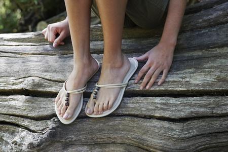 one teenage girl only: Teenage girl (16-17 years) wearing flip-flops sitting on tree trunk low section