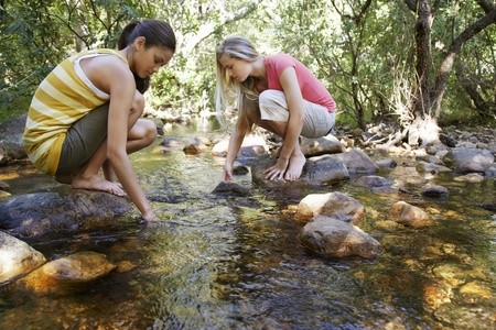 Two teenage girls (16-17 years) squatting on stone by stream in forest hands in water Stock Photo - 12514211
