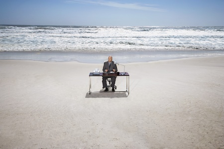 senior business man: Senior business man sitting at office desk on beach elevated view LANG_EVOIMAGES