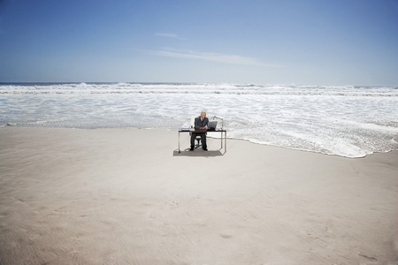 Senior business man sitting at office desk on beach elevated view Stock Photo - 12514224