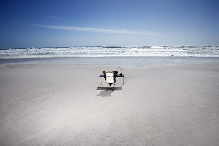 elevated view: Senior business man sitting at office desk on beach elevated view back view LANG_EVOIMAGES