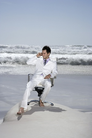 out of context: Man using mobile phone sitting on office chair on beach LANG_EVOIMAGES