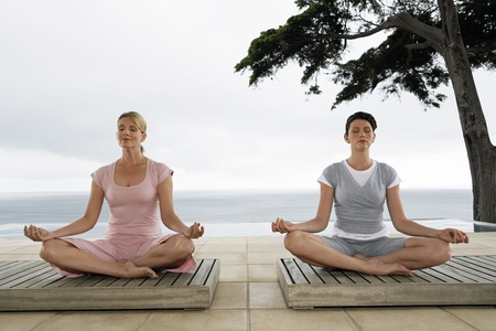 Two women sitting in yoga positions on terrace Stock Photo - 12514261